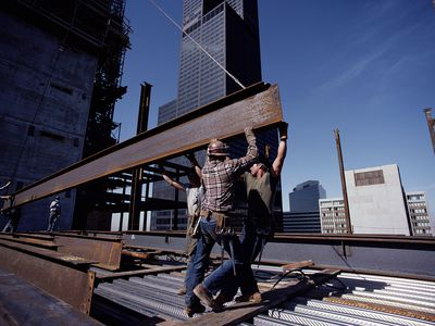 Construction workers carrying a steel beam, working under an indemnity clause.