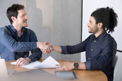 Two men shaking hands holding paperwork