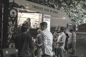 Group of customers in line at food truck at night