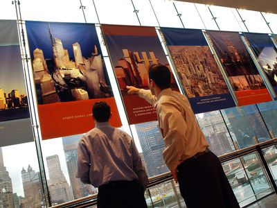 Two men looking and pointing at city plans hanging on windows