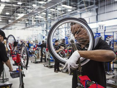 Male skilled factory worker assembling a bicycle in a factory, attaching a wheel.