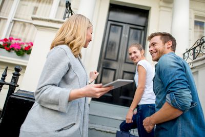 Couple smiling as agent as they walk up steps to a new house