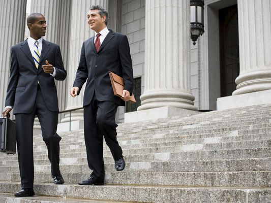 Two male lawyers talking on the steps of a courthouse