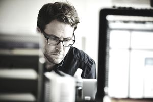 man with serious expression working at computer