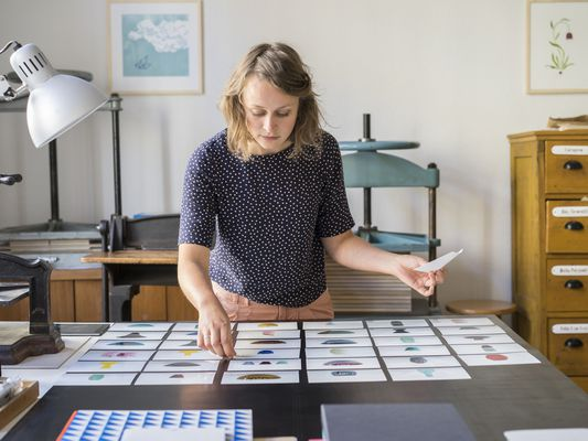 woman laying out photographs
