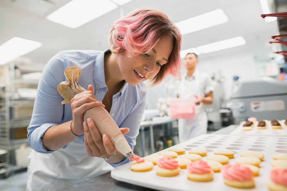 Pastry chef piping cookies pink icing commercial kitchen