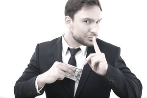 Man hiding money in his suit and raising his finger to his lips.