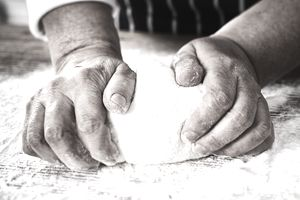 Close up of hands pressing on pizza dough.