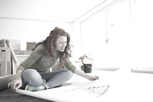 young woman sitting in apartment looking at blueprints