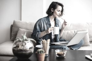 Woman using laptop on sofa and drinking coffee