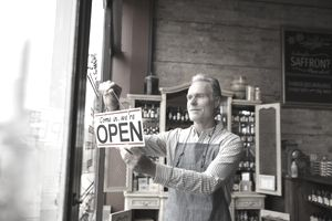 Shop owner hanging an open sign in the shop window of a small start-up stage business.