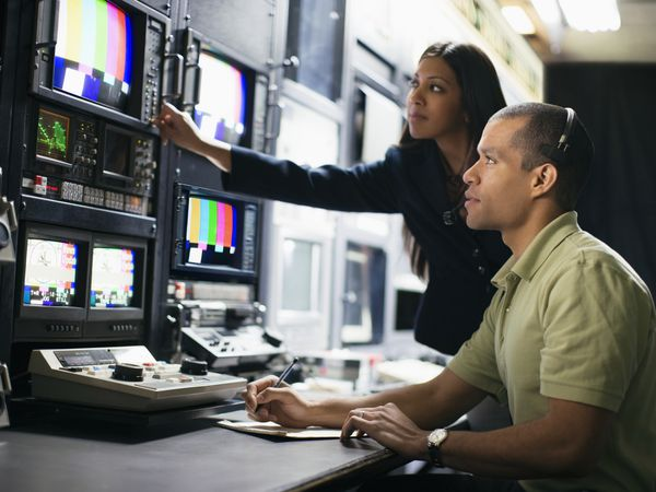 Man and woman working behind the scenes in tv studio