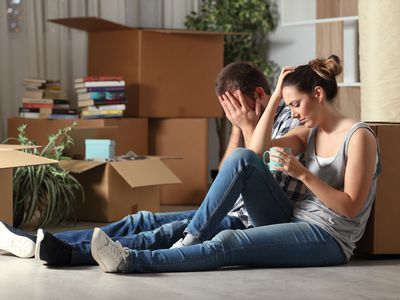 Sad evicted couple moving home complaining on the floor