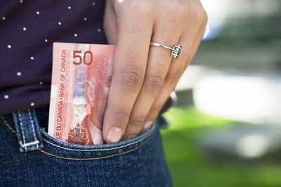 Close-up of a person's hand putting money in their pocket