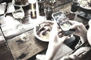 Woman taking photo of food with smartphone while having lunch with friends in restaurant