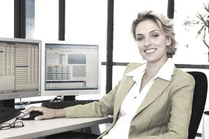 Businesswoman working on computers at her desk