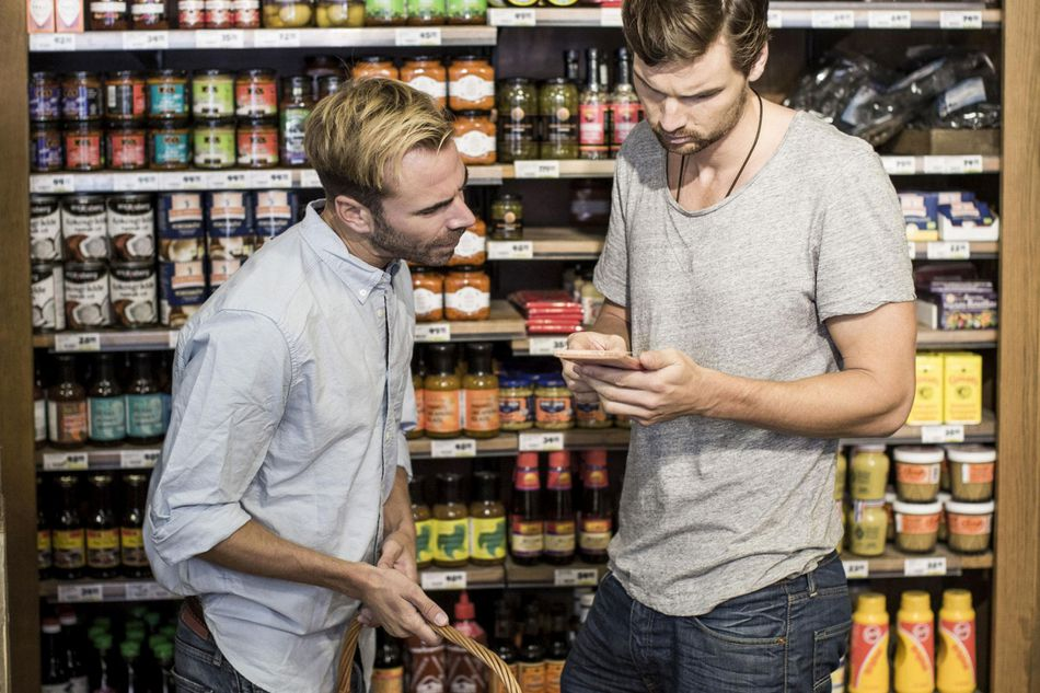 Young male friends reading label against shelf in supermarket