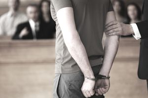 Closeup from the rear of a handcuffed man standing in courtroom