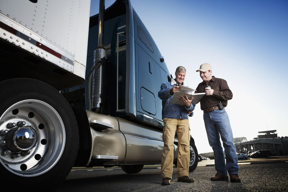 Men looking at paperwork next to freight truck