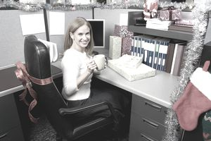 Woman in office cubicle decorated for Christmas