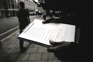 Hands of person holding clipboard of market research surveys on a city street