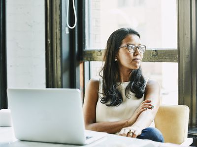 Businesswoman at laptop staring out window and thinking