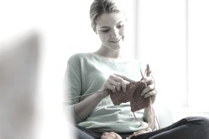 Young woman sitting in window seat knitting