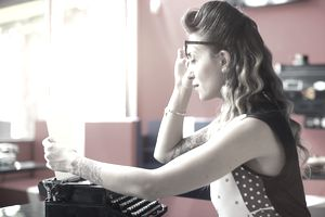 Woman looking at piece of paper in front of typewriter