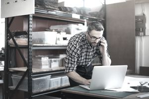 Shot of a man using a laptop and mobile phone while working on a project in a workshop