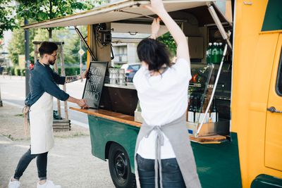 Male owner adjusting board on concession stand while female coworker opening shade of food truck