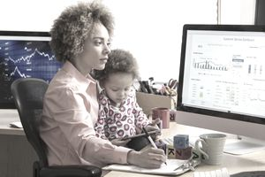 Woman with child in her lap comparing charts on computer