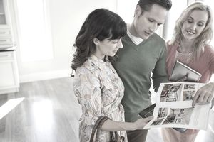 Female realtor showing new home brochure to couple