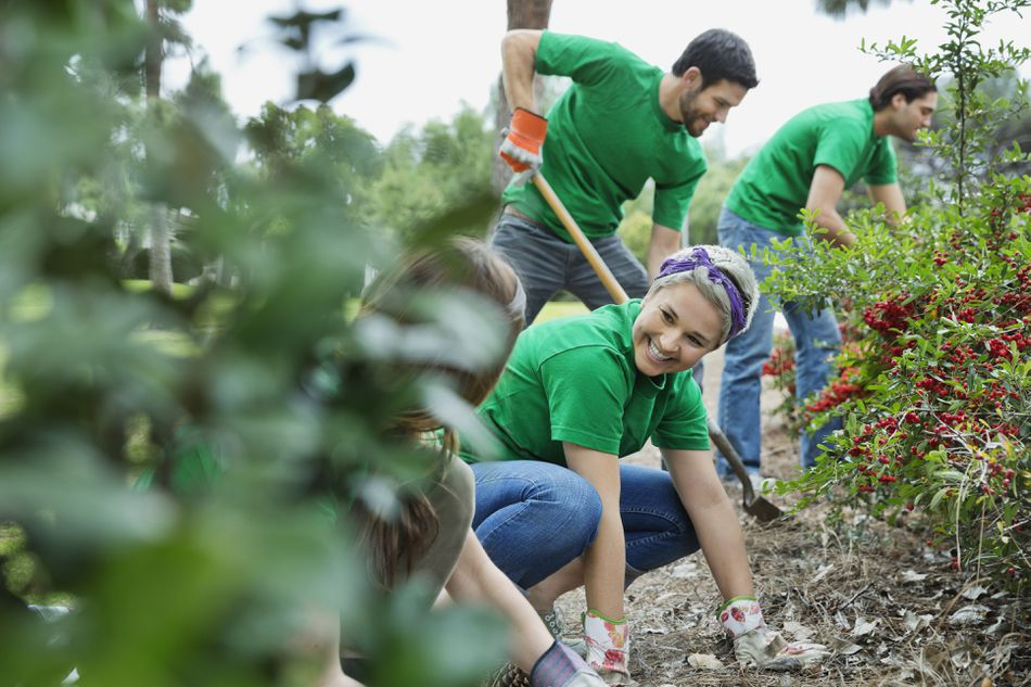 environmentalists with volunteers cleaning a city park