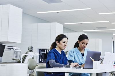 Hygienists using laptop together at desk in dental clinic