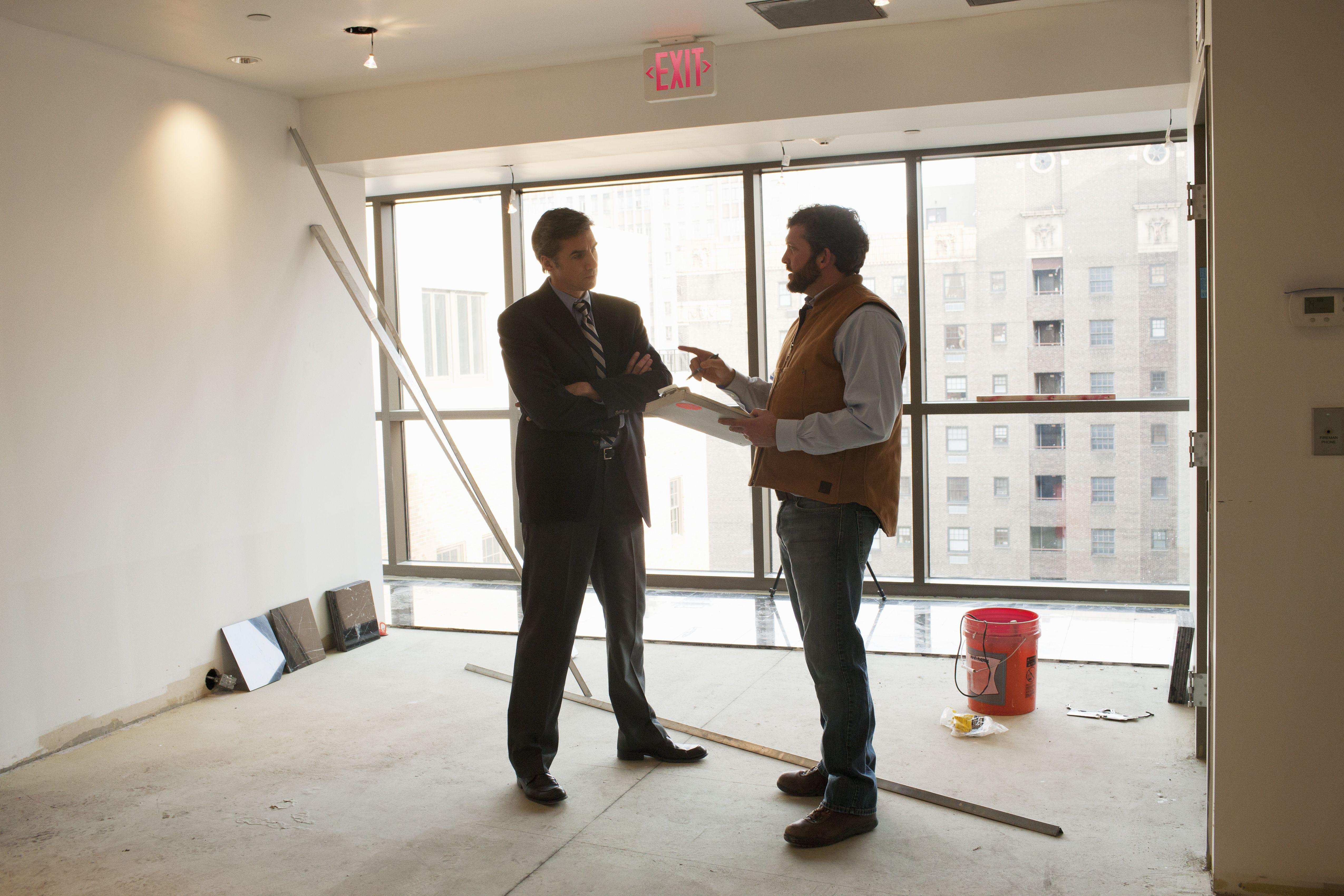 Manager talking to maintenance supervisor in empty room