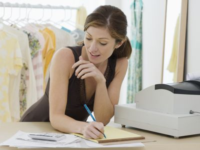 woman doing calculations in clothing shop