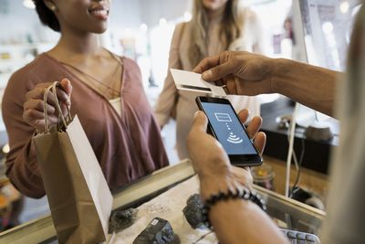 Customers paying shop owner using contactless payment cell phone credit card reader