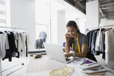 Woman working at laptop at her small clothing design business