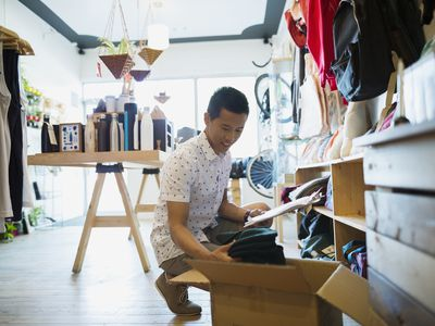 Shop owner with clipboard processing new merchandise