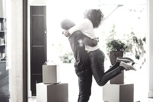 Happy man lifting woman in house with boxes