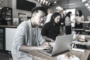 a group of young people in a coffee shop working on laptops