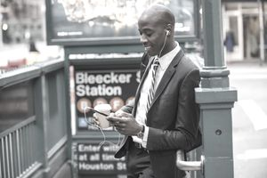 Man looking at a retail app on his smartphone on the streets of NYC.