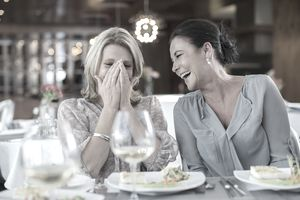 Two mature women laughing in restaurant