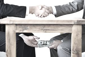 Two men shaking hands across a table while passing money to each other under the table.