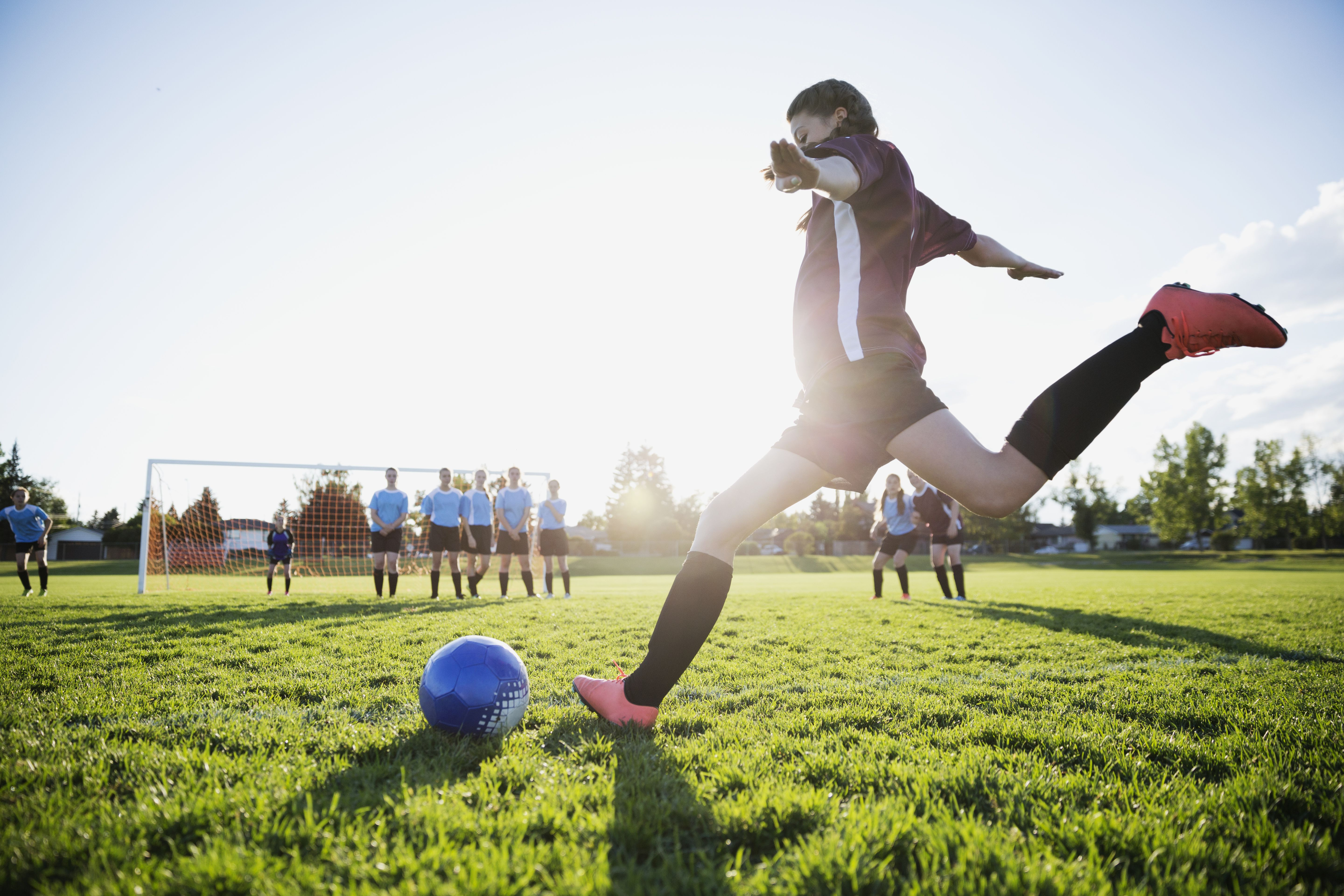 Middle school girl soccer player kicking free kick on sunny field