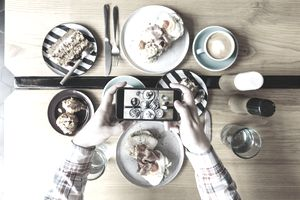 Man photographing food on table