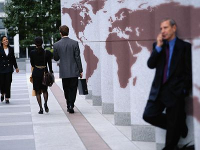 A group of business people by a map of the world.