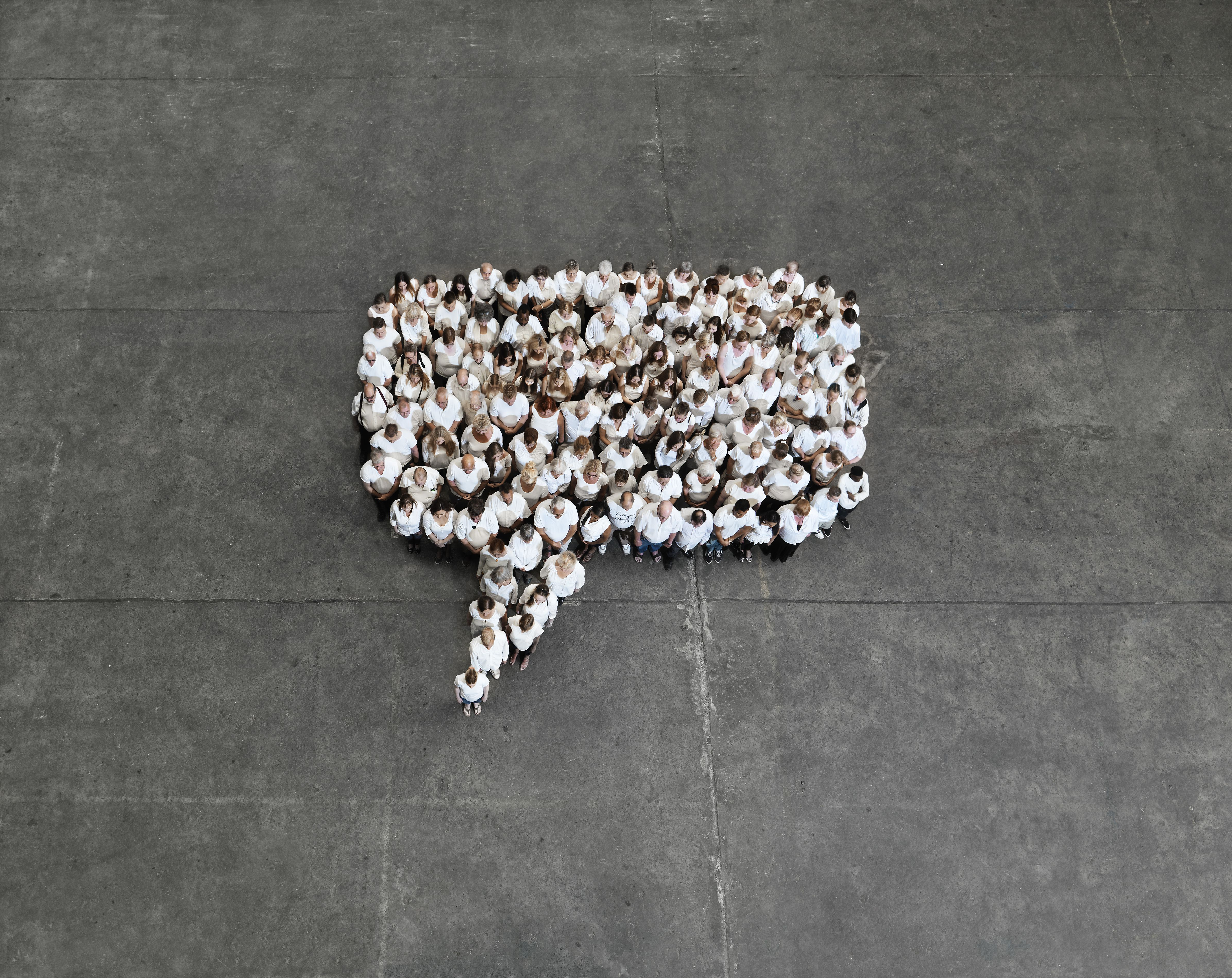 an aerial shot of people standing in the shape of a cartoon quote