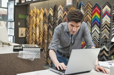 Owner of frame store using laptop computer to file his business taxes.