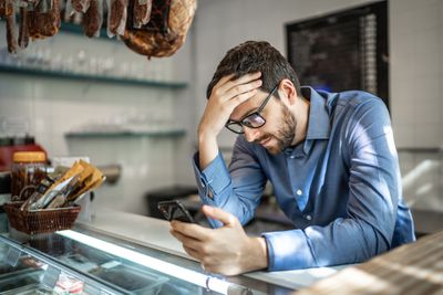 man in blue shirt on iphone in a store looking worried